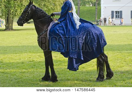 Woman dressed in medieval clothes sitting on a horse in middle ages festival