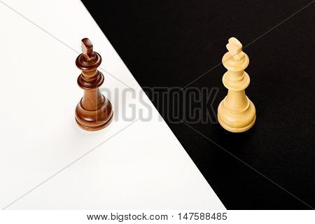 wooden chess kings on black and white abstract concept