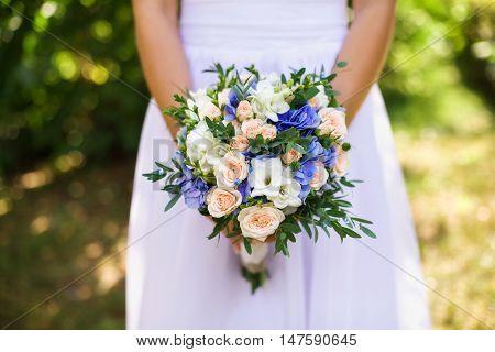 Beautiful wedding bouquet in bride's hands closeup selective focus