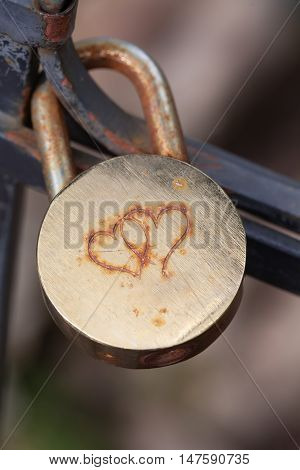 Aged and shabby closed padlock. Security concept. Macro view, soft focus