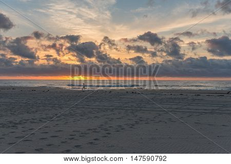 A solitary walker on the beach shortly after sunrise with steps etched in the sand leading to the ocean and orange sunlight straining to burst through dramatic cloud formations.
