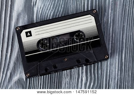 Music concept. Black audio cassette on the gray wooden background. Vintage, retro style. Soft focus photo