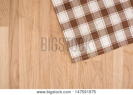 Checkered Tablecloth On The Wooden Background. Top view.