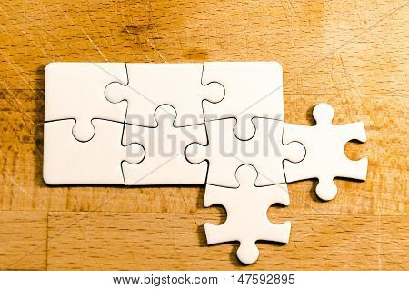 white jigsaw/puzzle whit new branches over a wooden table background symbol of problem solving and open mind