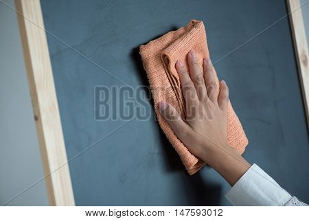 Close up of woman hand holding fabric for clean wooden blackboard.