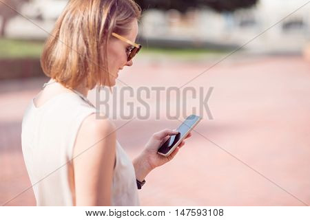 Always connected. A portrait of a positive and merry young woman using her smart phone while being outdoors