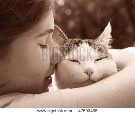 happy teen girl with cat close up sepia black and white portrait on the summer garden background