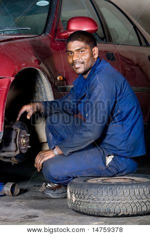 indian mechanic changing vehicle tyre