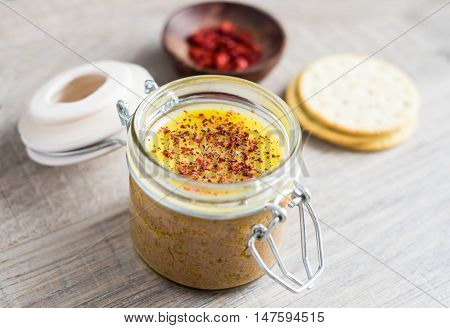 Homemade chicken liver pate in jars with wheat crackers, selective focus