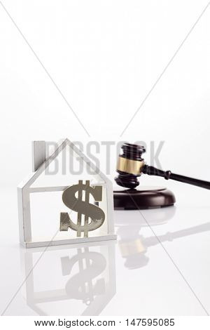 gavel hammer with model house with dollar sign on the white background