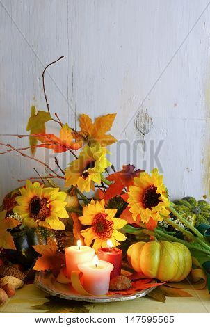 Thanksgiving or fall background with gourds candles autumn leaves twigs and sunflowers on a rustic wooden background with a vintage filter applied. Vertical orientation with copy space.