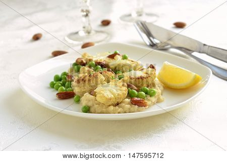 Salad with roasted cauliflower and green peas almonds served on vegetable puree