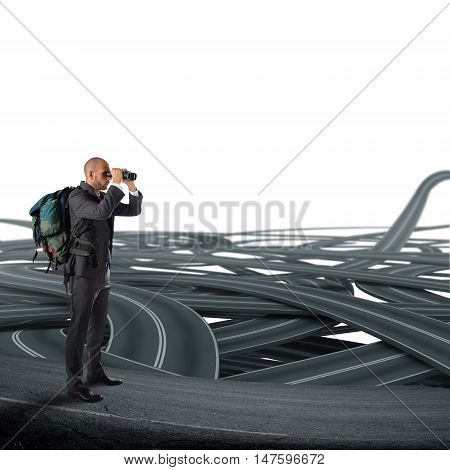 Businessman with backpack and binoculars watching a tangle of streets