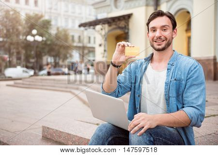 Convenient to pay. Overjoyed man holding gold card and laptop while sitting on steps outdoors