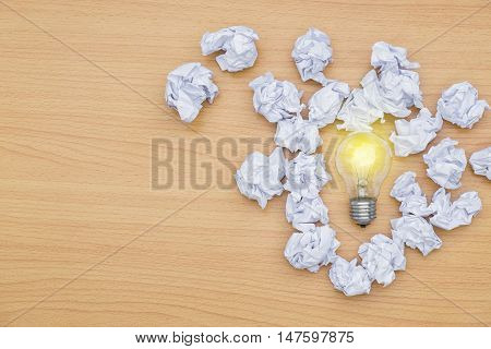 Idea concept incandescent bulb with lighting And crumpled paper