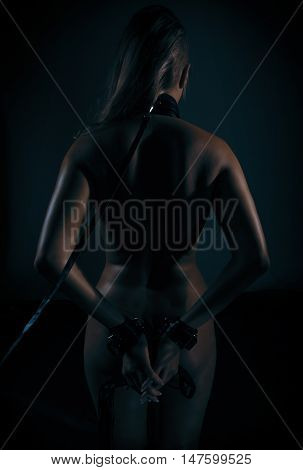 Low key photo of sexy female nude back and hands binded with cuffs and collar holding whip against dark background