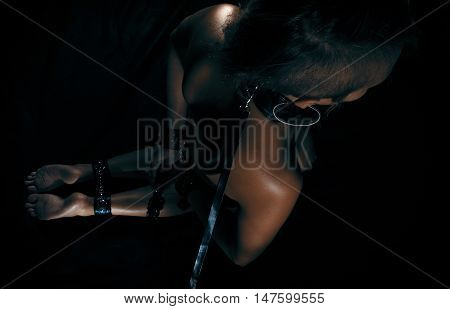 Low key photo of sexy female nude back and hands binded with cuffs and collar holding whip against dark background overhead horizontal view