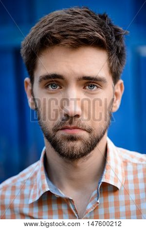 Close up portrait of handsome man upset looking at camera over blue background.