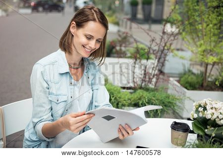 Nice time spending. Positive delighted charming woman sitting at the table and smiling while reading a magazine