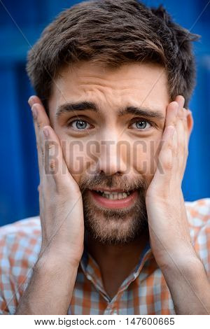 Close up portrait of handsome man upset holding face with hands, looking at camera over blue background.