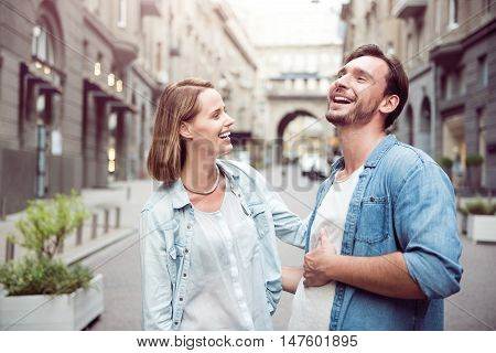 Involved in fun. Overjoyed smiling happy couple laughing and expressing positivity while having a walk
