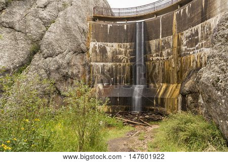 A narrow waterfall on a concrete dam.