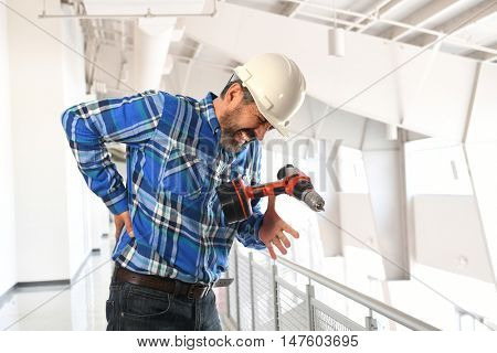 Hispanic worker getting injury to lower back inside building