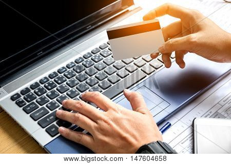 Online playments Hand holding Credit Card payments and using Laptop on desk vintage style