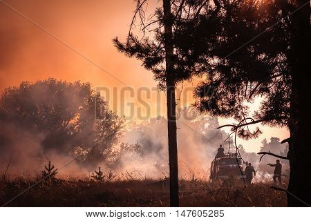 firefighters on the fire truck at sunset extinguish wildfire