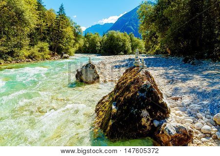 beautiful wild river with turquoise water and stone piles.
