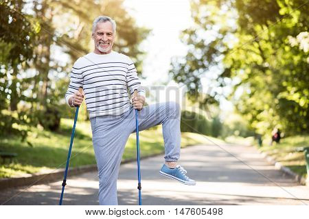Sunny morning. Smiley grey-haired man with beard doing morning exercises with tracksticks