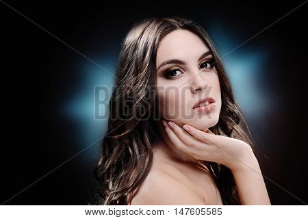 Beautiful young girl with long hair on dark background. Beauty concept.