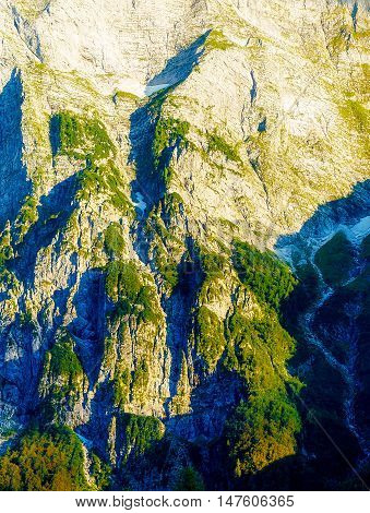 beautiful detail of alpine mountain rocks covered with moos on sunny day.