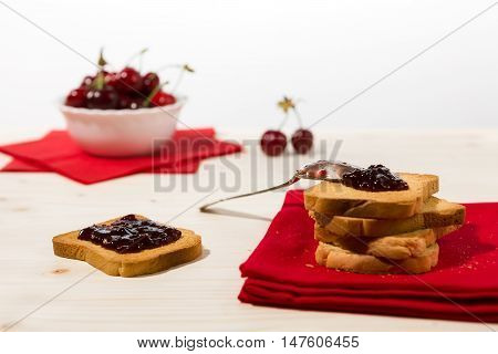 Rusk with cherry jam and cherry fruit on background