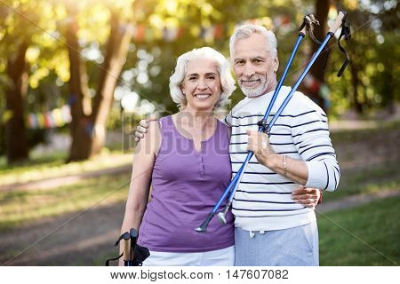 Accomplished. Smiley elderly man and woman hugging each other while holding tracking sticks