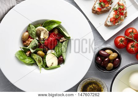 Italian salad with basil leaves, olives, capers, walnuts, mozzarella cheese and red pepper and traditional bruschetta on stone background.