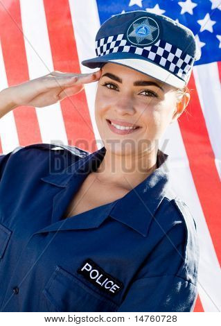 young american female police officer saluting, background is USA flag