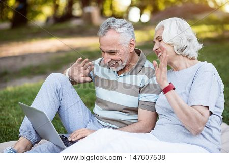 Cheerful morning. Good looking aged couple waving hands to the laptop screen, while sitting on the grass in park