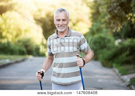 Youth is not your age. Handsome grandpa having exercises in the morning outdoors