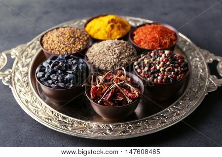 Different spices in bowls on tray