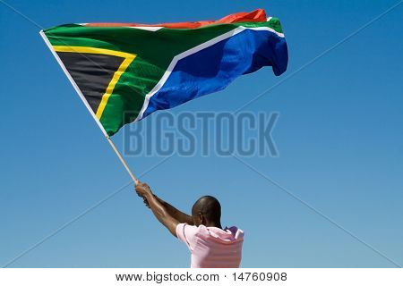 african man waving a south african flag on beach, new south africa 2010 concept
