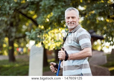 Way to go Good-looking old man in stripped t-shirt smiling and posing while getting ready to go jogging