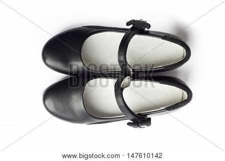 Top view on pair of black shoes for girl on white background