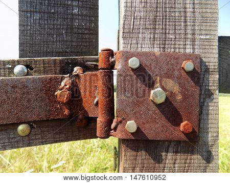 Old rusty hinges on wooden gate during day
