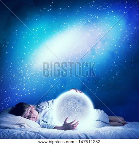 Cute boy in bed looking at glowing moon planet. Elements of this image are furnished by NASA