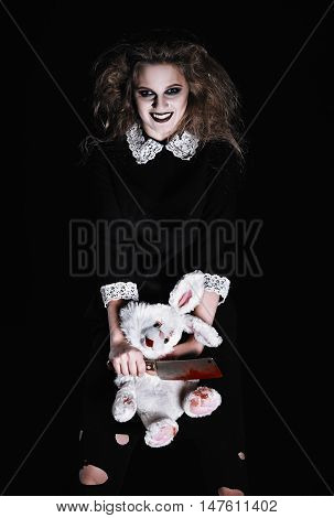 Horror shot: a scary wicked girl with rabbit toy and bloody cleaver in hands