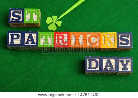 St Patrick's day spelled with colorful alphabet blocks displayed with a four leaf clover on a green background