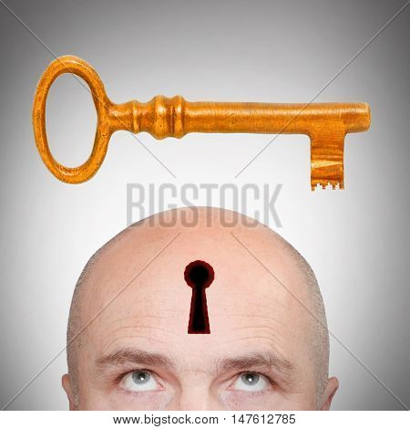 Man with locked head and golden key. Secrecy concept.