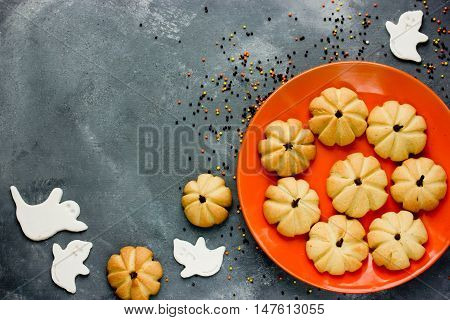 Pumpkin cookies and white sugar ghosts for Halloween treats for kids top view with copy space