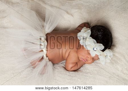 A peaceful newborn African American baby girl sleeps sweetly with a tutu and a floral headband. Taken from above.
